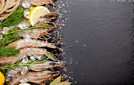 prawn: Fresh prawns with spices on black stone background. Top view with copy space