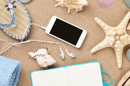 flip phone: Smartphone and notepad on sea sand with starfish and shells. Top view with copy space