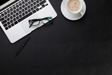 Mesa de cuero de la oficina con el ordenador portátil y una taza de café. Vista superior con espacio de copia