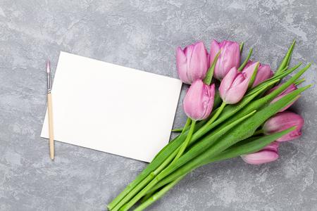 Fiori freschi del tulipano viola e biglietto di auguri vuoto sul tavolo di pietra. Vista dall'alto con lo spazio della copia
