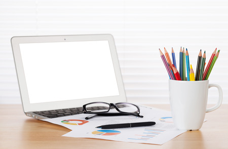 pencil holder: Office workplace with laptop, reports and pencils on wooden desk table in front of window with blinds Stock Photo