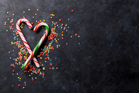 chocolate candy: Candy canes heart on dark stone background. Top view with copy space