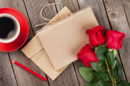 Love letter notepad, red roses and coffee cup on wooden table. Valentines day concept