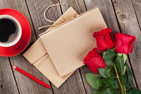 Liebesbrief Notizblock, rote Rosen und Kaffeetasse auf Holztisch. Valentinstag-Konzept