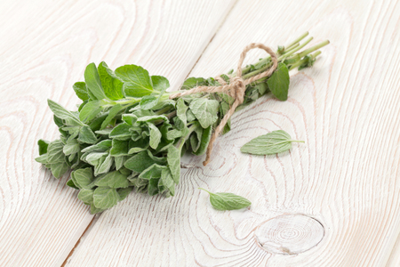 Bunch of garden oregano herb on wooden table