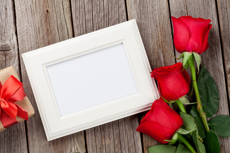 frame  box: Red roses, photo frame and gift box over wooden background. Top view with copy space Stock Photo