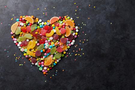 candies: Caramelos de colores, jalea y mermelada de corazón en el fondo de piedra. Vista superior con espacio de copia