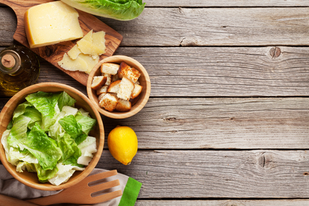 ensalada cesar: Fresh healthy caesar salad cooking on wooden table. Top view with copy space