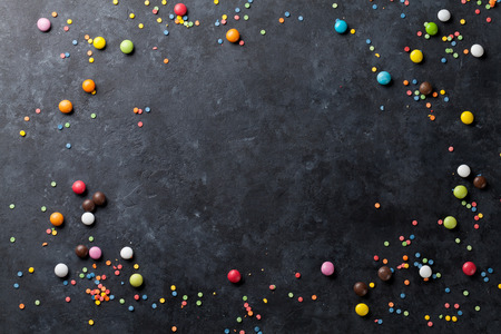 candy border: Colorful candies frame on stone background. Top view with copy space