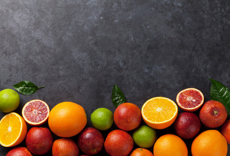 jugo de frutas: Fresh citruses on dark stone background. Oranges and limes. Top view with copy space