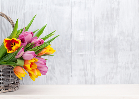Fresh colorful tulip flowers bouquet on shelf in front of wooden wall. View with copy space