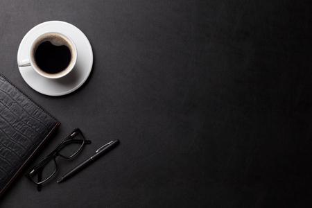 オフィスのコーヒー カップ、メモ帳とペンで革デスク テーブル。コピー スペース平面図