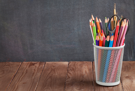 pencil holder: School and office supplies on classroom table in front of blackboard. View with copy space