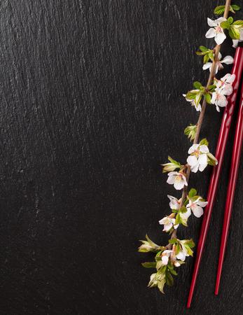 日本の寿司箸、黒い石の背景に桜の花。コピー スペース平面図 写真素材