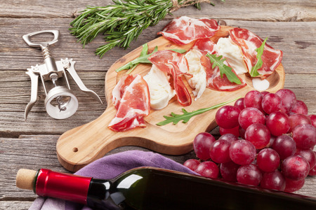 Prosciutto and mozzarella with red wine on wooden table Stock Photo