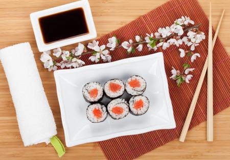 table set: Sushi maki set and sakura branch on bamboo table Stock Photo