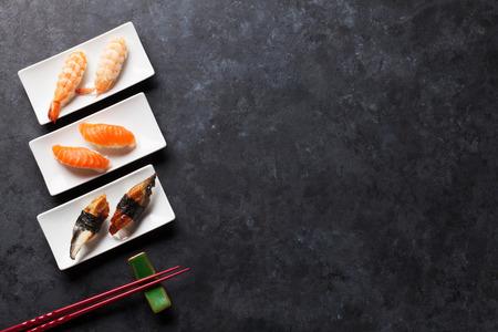 De reeks van sushi en eetstokjes op stenen tafel. Bovenaanzicht met een kopie ruimte