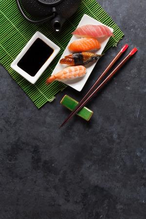 comida japonesa: Conjunto de sushi y té verde en la mesa de piedra. Vista superior con espacio de copia