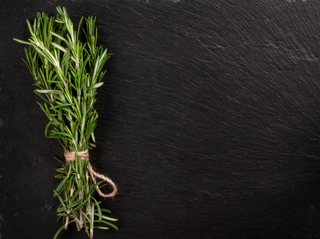 Rosemary herb bunch over stone background. Top view with copy space