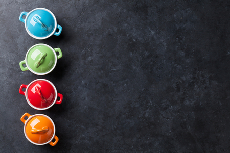 clean dishes: Colorful saucepans on stone table background. Top view with copy space Stock Photo