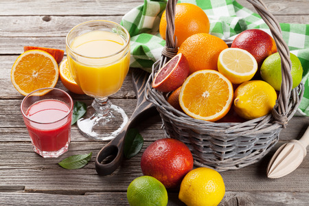 Citrus fruits in basket and juice glasses. Orange, lemon, lime.