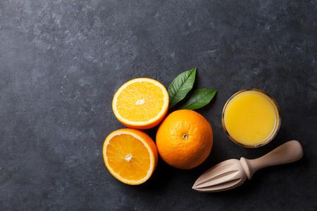 Sinaasappelen en sapglas op steenachtergrond. Bovenaanzicht met kopie ruimte