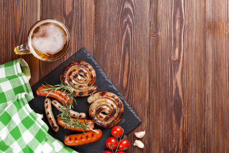 german sausage: Grilled sausages and beer mug on wooden table. Top view with copy space