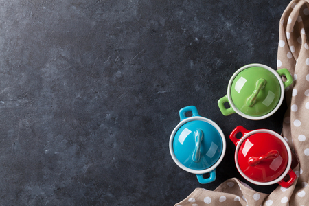 Colorful saucepans on stone table background. Top view with copy space Stock Photo