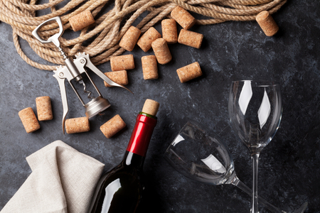 Wine, glasses and corkscrew over stone background. Top view 免版税图像