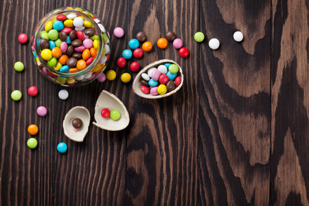 copies: Colorful candies on wooden background. Top view with copy space