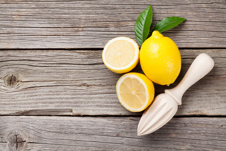 lemon slice: Fresh lemons and juicer on wooden table. Top view with copy space