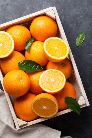 Fresh ripe oranges in wooden box on dark stone background. Top view