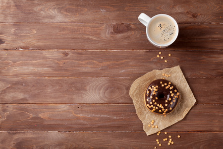 coffee table: Donut and coffee on wooden table. Top view with copy space Stock Photo