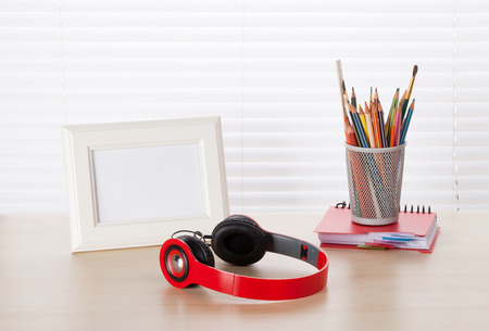 wood blinds: Office workplace with photo frame, headphones and pencils on wood desk table in front of window with blinds