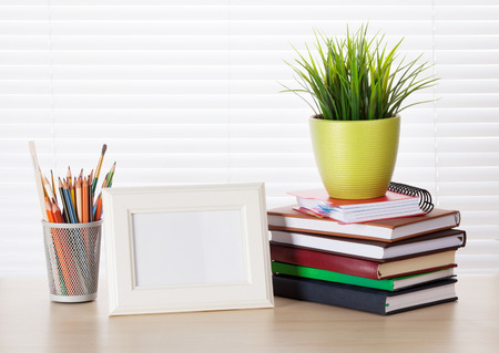 photo frame: Office workplace with photo frame, books and pencils on wood desk table in front of window with blinds