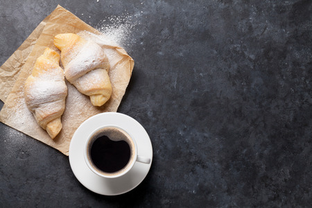 Fresh homemade croissants and coffee on stone table. Top view with copy space Banque d'images