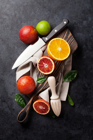 citrus: Fresh citruses on dark stone background. Oranges and limes. Top view