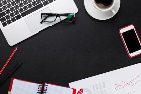 papel de notas: Mesa de cuero de la oficina con el ordenador portátil, la taza de café, bloc de notas y teléfono. Vista superior con espacio de copia