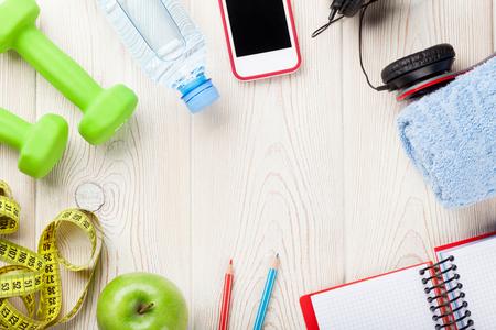 forme et sante: Concept de santé et de conditionnement physique. Haltères, bouteille d'eau, smartphones, écouteurs et bloc-notes. Vue de dessus avec copie