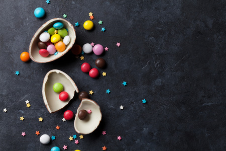 chocolate egg: Colorful candies and chocolate egg on stone background. Top view with copy space Stock Photo