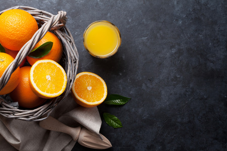 vegetarian food: Fresh orange fruits and juice on stone table. Top view with copy space