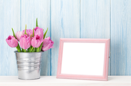 colorful frame: Fresh pink tulip flowers bouquet and blank photo frame with copy space on shelf in front of wooden wall