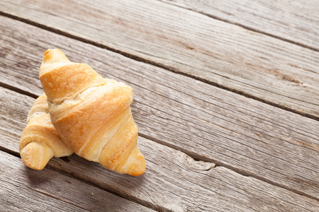 traditionally french: Fresh homemade croissants on wooden table. View with copy space