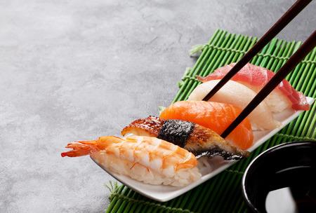 Sushi en eetstokjes op stenen tafel. Bekijken met kopie ruimte
