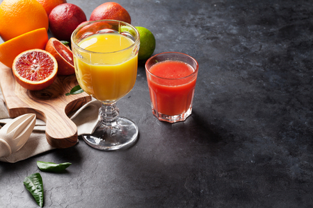 vegetarian food: Fresh citruses and juice on dark stone background. Oranges and limes. View with copy space