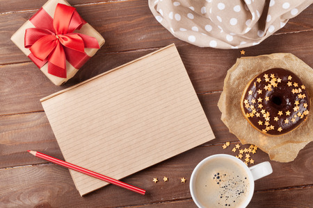 Notepad, donut and coffee on wooden table. Top view with copy space
