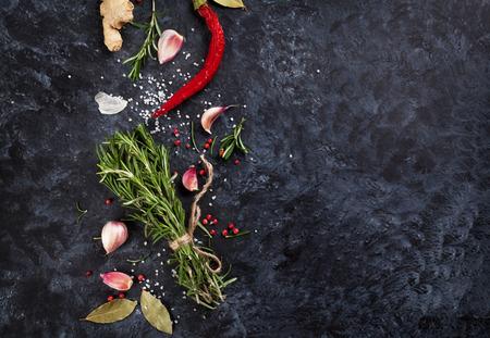 Kruiden en specerijen op zwarte steen achtergrond. Bovenaanzicht met een kopie ruimte
