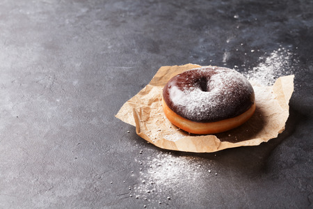 donuts: Chocolate donut with sugar powder on stone table Stock Photo