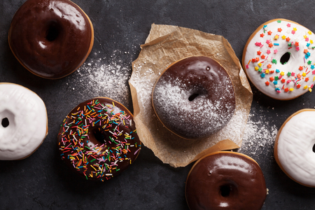 table top: Colorful donuts on stone table. Top view