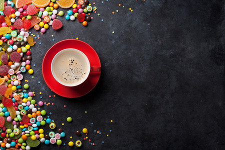cafe bombon: Colorful candies, jelly and marmalade and coffee cup on stone background. Top view with copy space